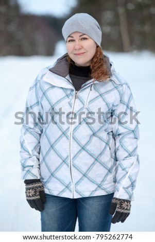 Young Caucasian woman in a winter jacket is outdoor at wintry weather