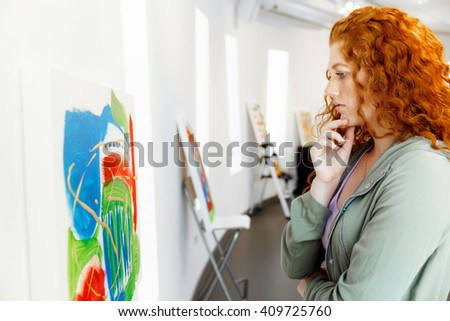 Young caucasian woman in art gallery front of  paintings