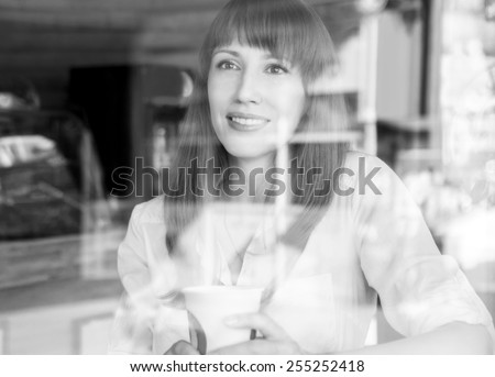 Young caucasian woman in coffee house at summer morning. Pretty girl with cup of coffee behind glass. Black and white image - stock photo