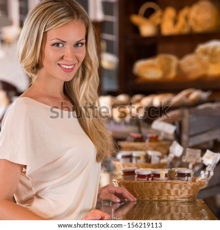 Young caucasian woman in front of bakery food store window, smiling and looking at camera