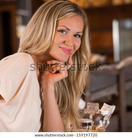 Young caucasian woman in front of bakery food store window, smiling and looking at camera - stock photo