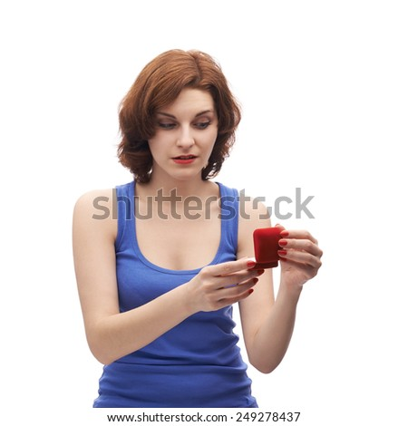 Young caucasian woman in her twenties holding opened red wedding ring box, isolated over the white background