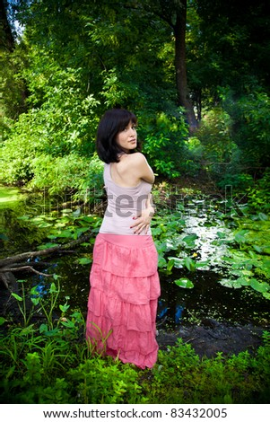 Young caucasian woman in pink dress standing near river in forest