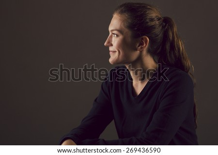 Young Caucasian woman in profile looking off camera and smiling with Rembrandt lighting - stock photo