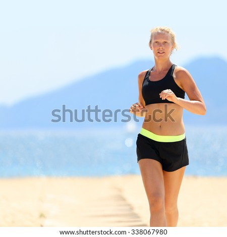 Young Caucasian woman in sportswear running at beach. Determined slim female is jogging on sunny day. She is representing healthy and fit lifestyle. - stock photo