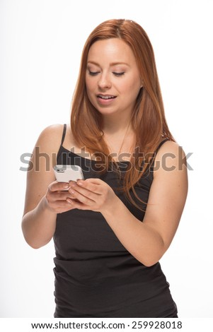 Young Caucasian woman in studio texting on smart phone - stock photo