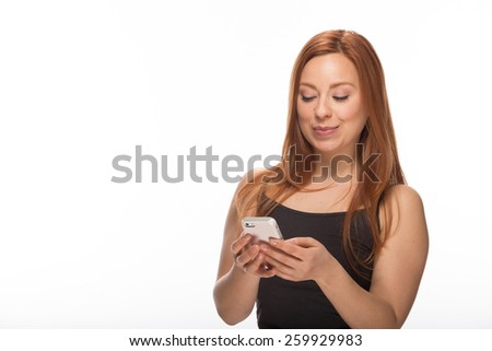 Young Caucasian woman in studio texting on smart phone