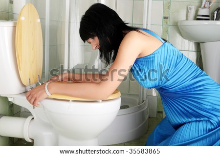 Young caucasian woman in toilet - pregnant,drunk or illness concept - stock photo