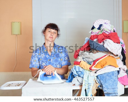 Young Caucasian woman ironed clothes in the room near the window.