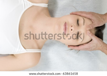 young caucasian woman lying down receiving head massage - stock photo