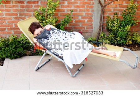 young caucasian woman lying in outdoor chair hiding by her skirt