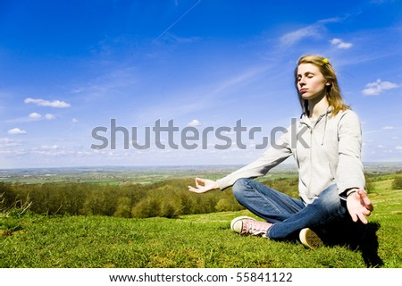 Young caucasian woman meditating outdoors in front of a bright blue sky and green countryside
