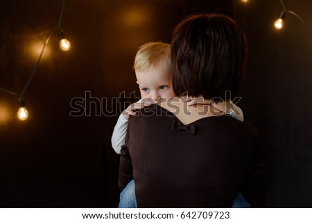 young Caucasian woman mother comforting her sad little toddler boy son on a black background, parenthood lifestyle concept
