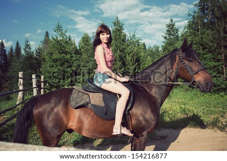 Young caucasian woman on her brown horse in a countryside landscape at summer