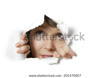 Young Caucasian woman peeking from ripped paper hole