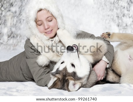 Young caucasian woman play with a malamute puppy - stock photo