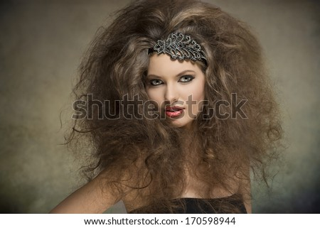 young caucasian woman posing in fashion portrait with voluminous curly hair-style, glitter accessory in the hair and cute make-up  - stock photo