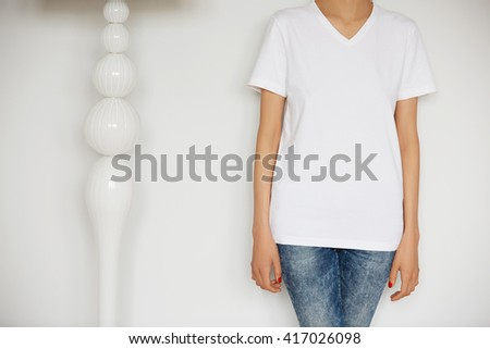 Young Caucasian woman posing indoor against home interior background. Cropped shot of hipster teenage girl wearing blank white T-shirt with copy space for your promotional content. Lifestyle concept.  - stock photo