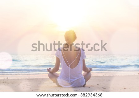 young caucasian woman practicing yoga at sunrise beach