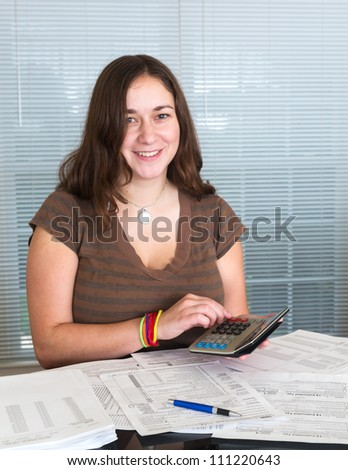 Young caucasian woman preparing tax form 1040 for tax year 2012  with receipts and calculator