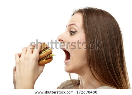 Young caucasian woman preparing to bite a big burger, isolated on white background