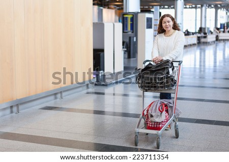 Young Caucasian woman pulling luggage hand-cart in airport hall - stock photo