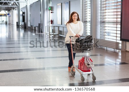 Young Caucasian woman pulling luggage hand-cart with bags along airport hall. Passenger in waiting area. - stock photo