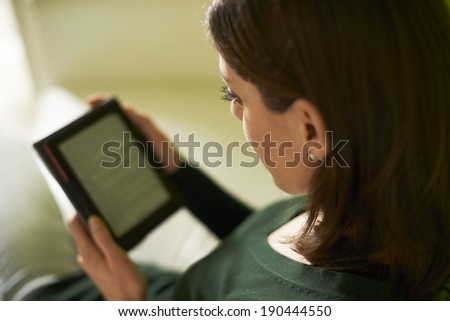young caucasian woman reading ebook at home, sitting on sofa and smiling - stock photo