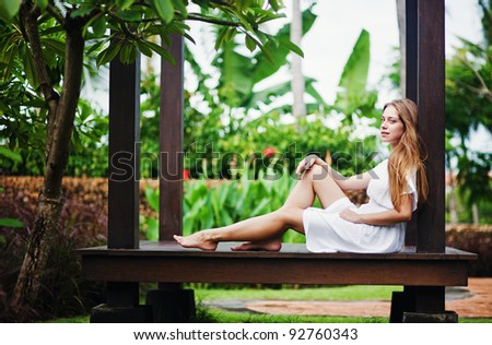 Young caucasian woman sitting on the bench - stock photo