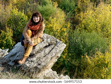 Young caucasian woman sitting on the rock over the autumn forest.