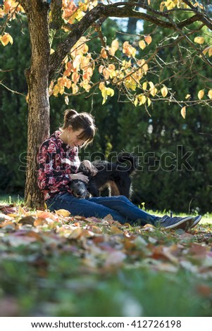 Young Caucasian woman sitting under an autumn tree cuddling her black dog. - stock photo
