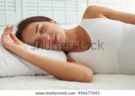 Young Caucasian woman sleeping in a relaxing pose in the bed, she is sleeping on the right side and she puts her hand on the pillow