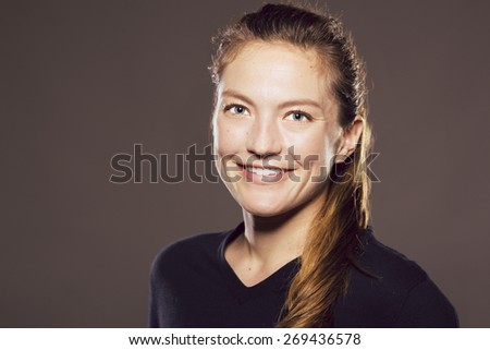 Young Caucasian woman slightly turned away looking at viewer while smiling - stock photo