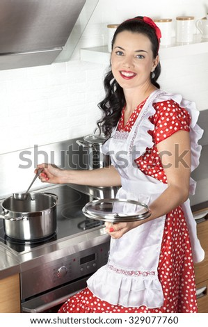 Young Caucasian woman standing by the stove in the kitchen, cooking soup - stock photo
