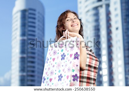 Young caucasian woman standing in city with shopping bags. Smiling and looking at camera. - stock photo