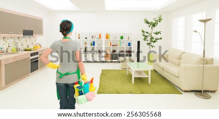 young caucasian woman standing in clean house holding cleaning products, looking at tidy room - stock photo