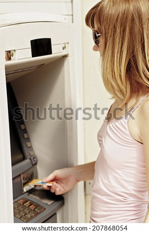 Young caucasian woman standing near an ATM holding a credit card.