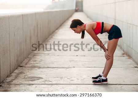 Young caucasian woman taking breath after jogging. Female athlete resting with hands on knees and looking away at sunset - stock photo