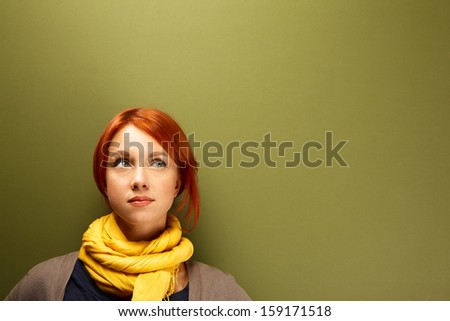 Young caucasian woman thinking near the green wall - stock photo