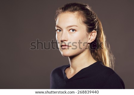 Young Caucasian woman turned three quarters towards camera with neutral expression - stock photo