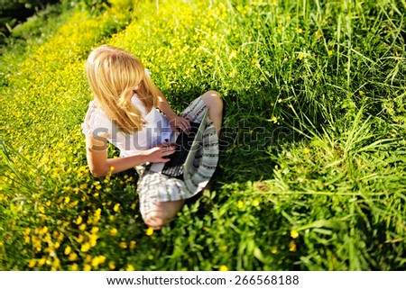 Young Caucasian woman using Laptop (Netbook) on nature, sitting in the grass in the park. - stock photo