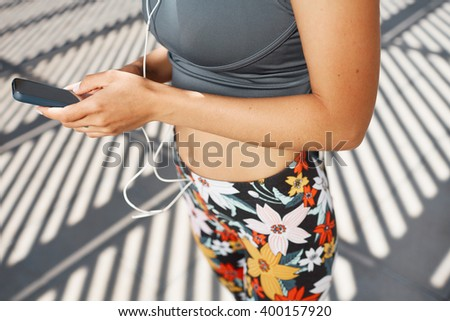Young caucasian woman wearing sports wear looking at mobile phone. Female athlete listening music with cell phone. Girl runner enjoying the sun and listen music in earphones from smartphone. - stock photo