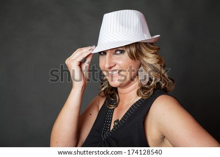 Young Caucasian woman wearing white pinstripe hat in studio - stock photo