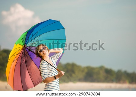 Young caucasian woman wearing white sunglasses with colourful rainbow umbrella looking at ocean on the Jimbaran beach on Bali before sunset. Travel, holidays, vacation, healthy lifestyle, tranquility - stock photo