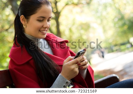 Young Caucasian woman with a cell phone, sitting in a park on a wooden bench, reading a SMS. - stock photo