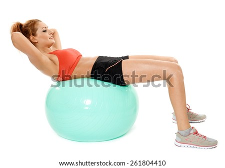 Young caucasian woman with a gym ball doing abs crunches, isolated on white - stock photo