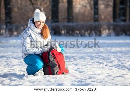 Young Caucasian woman with backpack in winter park, copyspace - stock photo
