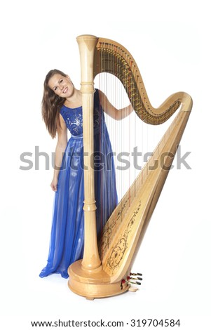 young caucasian woman with concert harp stands and smiles in studio against white background