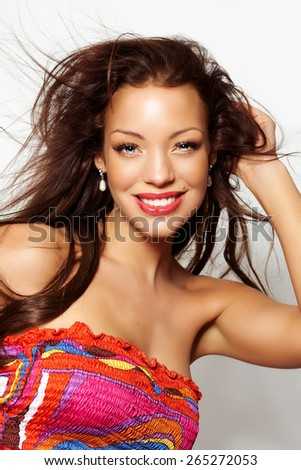 Young Caucasian woman with long brown hair posing in studio wearing silk colorful dress.