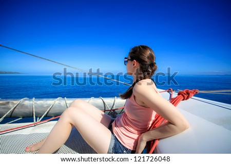 Young caucasian woman with plaited hair sitting on a boat in the sun in the middle of the sea sailing over smooth sea.